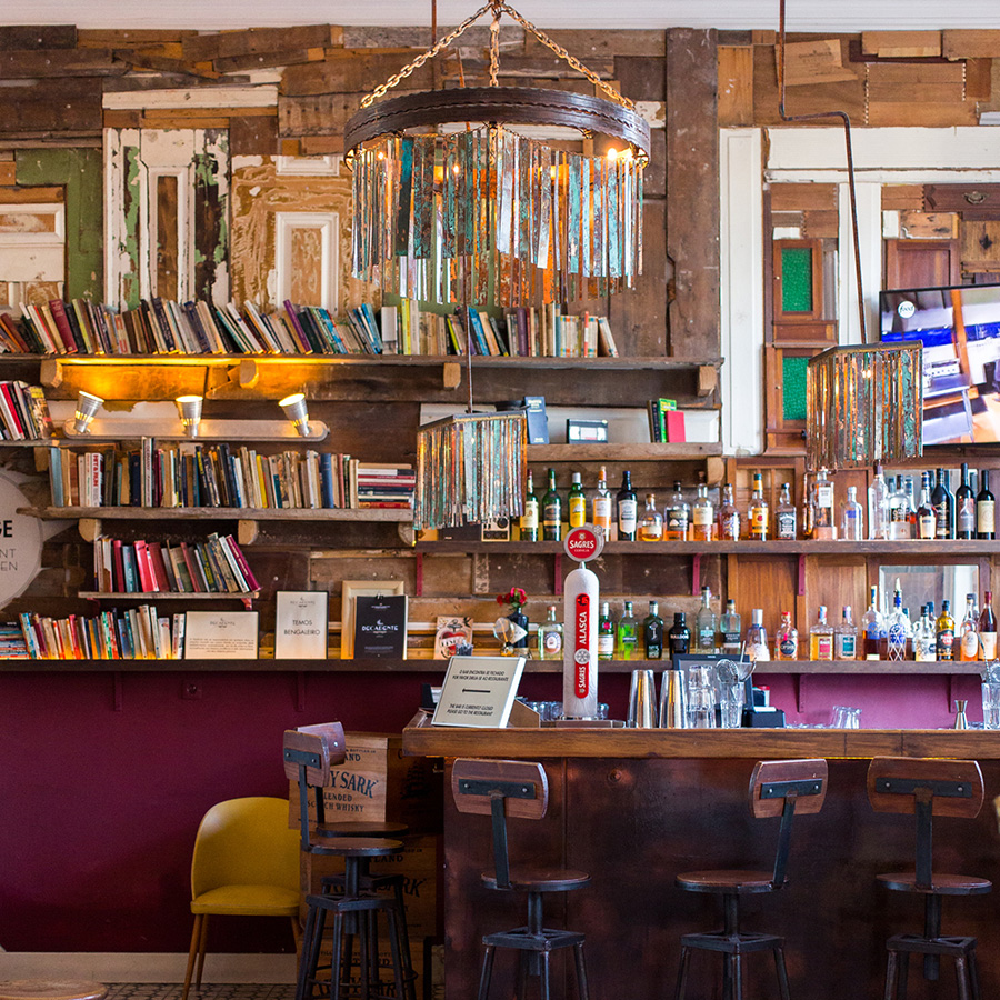 The Decadente bar, with shelves full of books and spirits and an assortment of vintage chairs